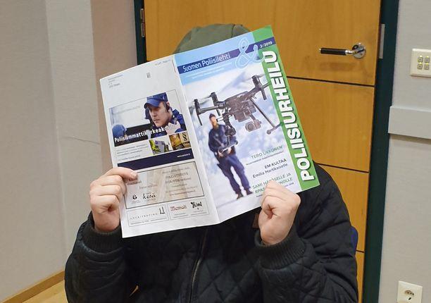 Nuori mies peitti kasvonsa Poliisiurheilu-lehdellä keskiviikkona oikeudessa.