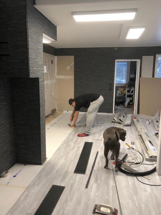 Aki Manninen asentaa lattiaa ja Putin-koira ihmettelee vieressä remonttia.