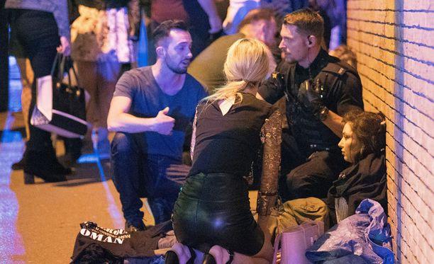 Uhrien hätä oli kova. Selviytyjät yrittivät auttaa loukkaantunutta naista seinän vierellä.