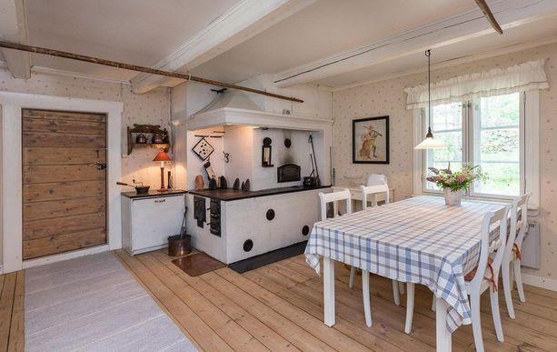 Vanha puuhella tuo hurmaavan tunnelman keittiöön. Romanttinen tapetti, kappaverhot ja muut sisustuselementit tekevät kokonaisuudesta maalaisromanttisen. Huomaa myös katossa oleva leipävarras.