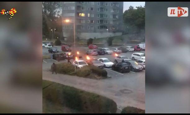 Videolla näkyy, kuinka tummiin pukeutunut joukko sytyttää tuleen parkkipaikan autoja.