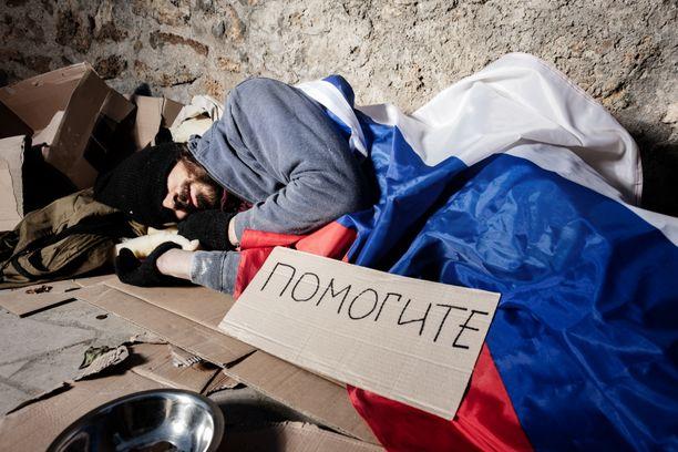 """Venäjän lippuun kääriytyneen miehen kyltissä lukee """"auttakaa"""". Lähes puolella venäläisistä ei ole rahaa kuin välttämättömään, selviää tuoreesta tutkimuksesta."""