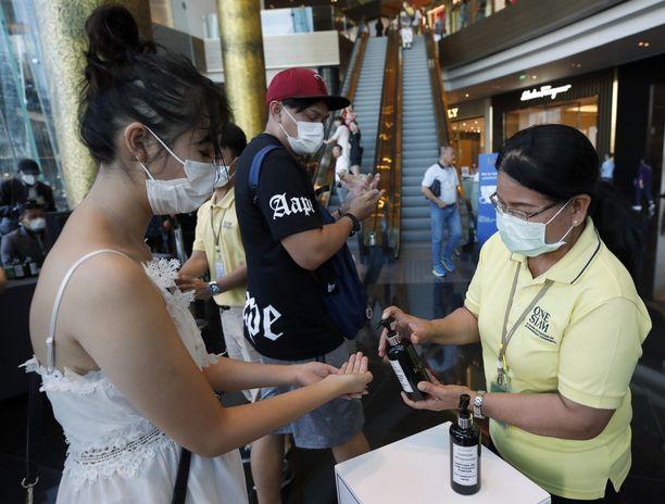 Työntekijä antaa desinfiointiainetta kiinalaiselle turistille Bangkokissa Thaimaassa.