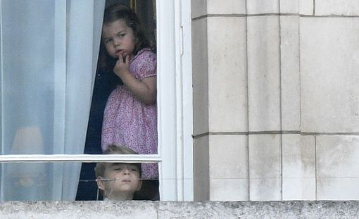 Prinssi George ja prinsessa Charlotte kurkkimassa Buckinghamin palatsin ikkunassa.
