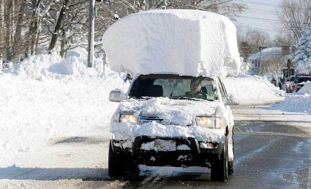 Tämä herra unohti pyyhkiä lumet auton katolta.