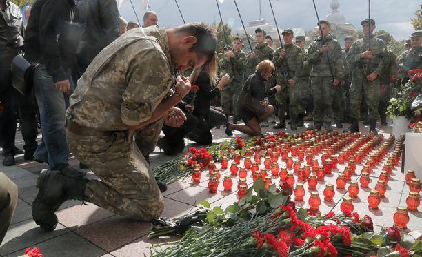 Varusmies polvistuneena kolmen viranomaisen kuoleman vuoksi. Viranomaiset menehtyivät terroristien iskussa Kiovassa sijaitsevaan parlamenttirakennukseen elokuun viimeisenä päivänä.