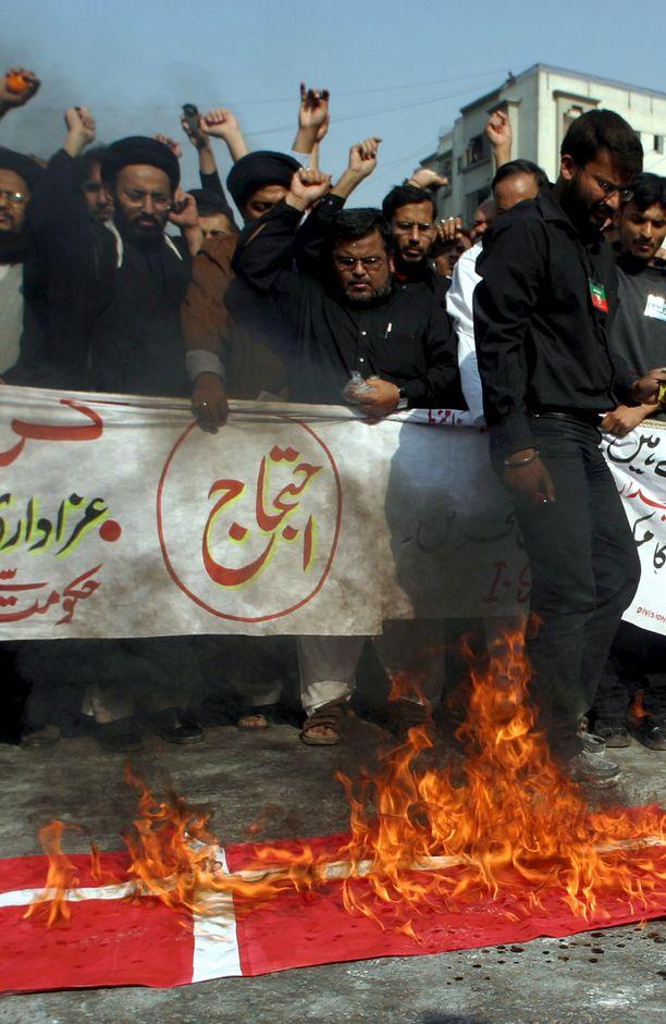 Tanskan lippuja poltettiin eri puolilla maailmaa, kun pilapiirroskohu levisi talvella 2006. Kuva Pakistanista.