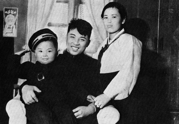 Pieni Kim Jong-il (vas.) perhepotretissa vanhempiensa seurassa.