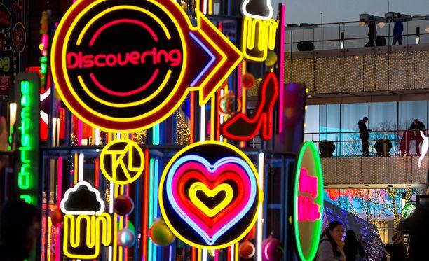 Joulun kaupallinen luonne on helposti nähtävissä Kiinassa. Shoppailijat nauttivat neonvalojen loisteesta kauppakeskuksessa Pekingissä.