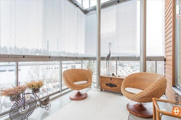 Kerrostalon korkea lasitettu parveke on sisutettu korikalusteilla ja rustiikkisella arkulla.
