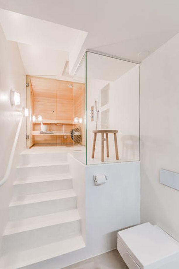 Tässä kylpyhuoneessa saunaan noustaan ylellisiä portaita pitkin. Huomaa vaaleat puulauteet ja lasiseinien tilantuntua luova vaikutus.