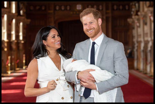 Prinssi Harry pitää sylissään esikoistaan. Vierellä Sussexin herttuatar Meghan.