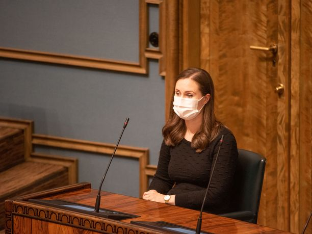 Pääministeri Sanna Marin (sd) kuunteli opposition moitteita ministeriaitiossa hengityssuojain naamallaan.