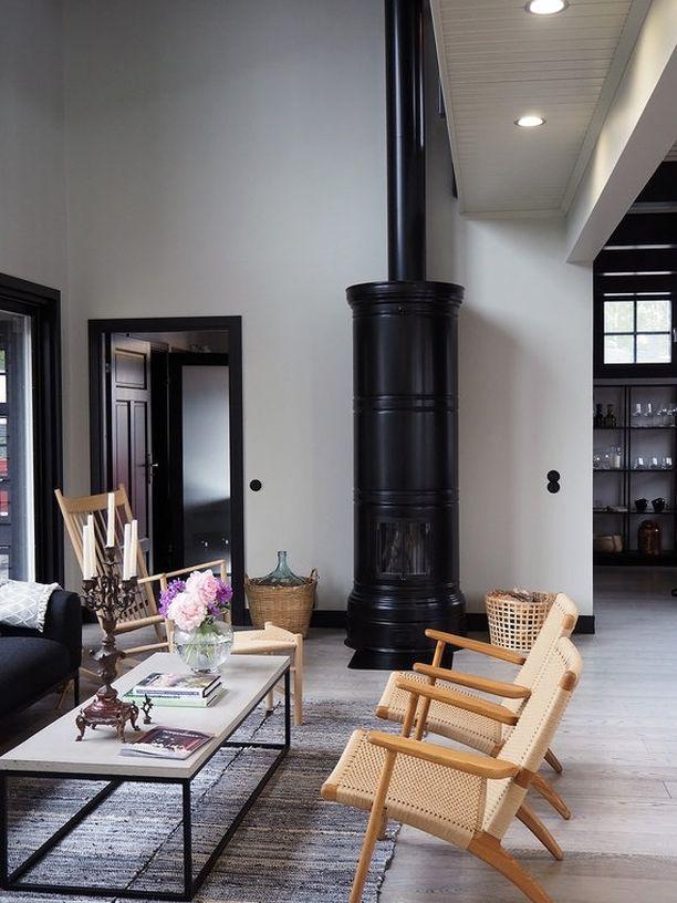 Mustassa pönttöuunissa yhdistyy moderni väri sekä maalaisromanttinen tyyli hauskalla tavalla.