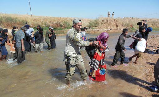 Irakilaissotilas auttoi naista joen yli Kirkukin lähellä viime viikolla. Lähes tuhat siviiliä on saapunut Hawijahista turvallisemmille alueille lähelle Kirkukia.