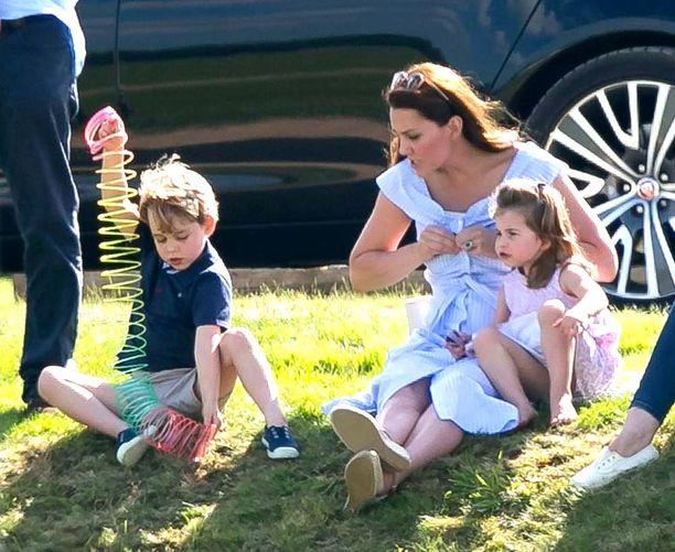 Prinssi George ja prinsessa Charlotte kesäisellä nurmikolla.