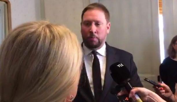 Kuvakaappaus valtioneuvoston videosta, jossa näkyy Paavo Arhinmäen (vas) kiihtynyt puuttuminen Leena Meren (ps) puheisiin. Tökkäämistä ei videolla näy.