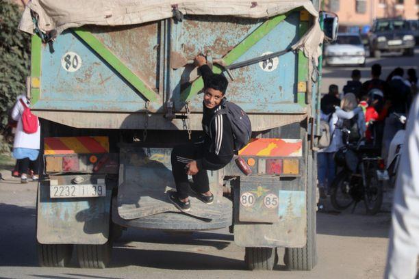 Marrakechin liepeillä Marokossa nähty vaarallinen urheilulaji. Koululaiset roikkuivat kuorma-auton perälaudassa. Tässä ensimmäinen kaveri mukana, kohta muut seurasivat perässä.