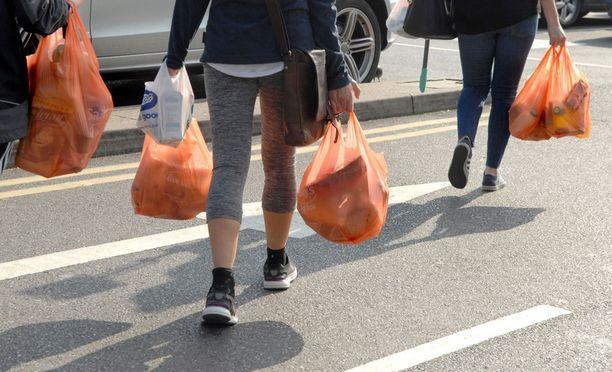 Britit ovat käyttäneet perinteisesti paljon muovipusseja. Muovipussien kantajia Lontoossa.