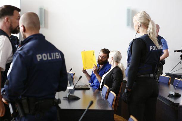 Raymond Granholm laski kasvoja peittäneen keltaisen kansion nopeasti torstain vangitsemisoikeudenkäynnissä.