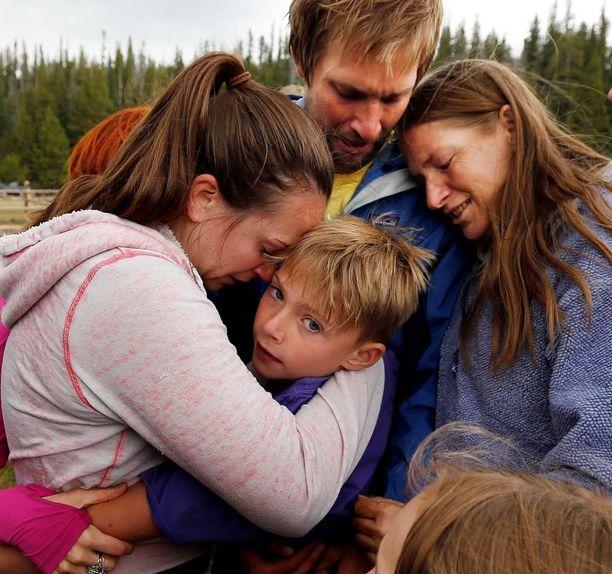 Malachi Bradley perheensä syleilyssä seikkailun jälkeen.
