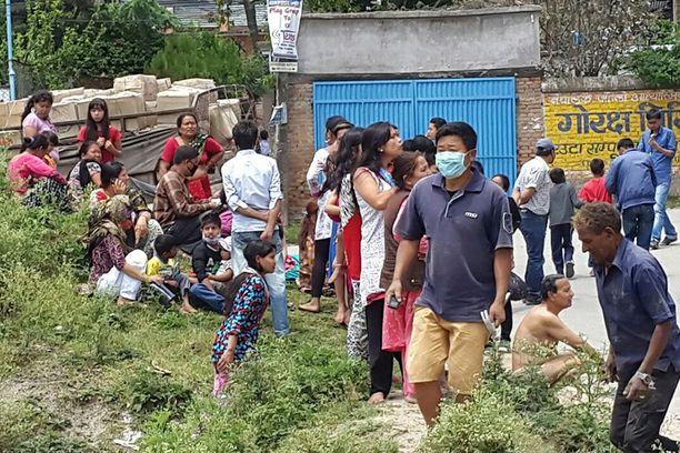 Ihmiset pakenivat vauhdilla kaduille Kathmandussa.