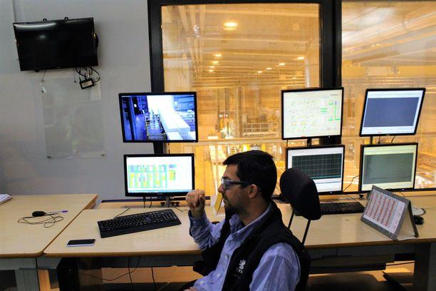 Työntekijät seuraavat automatisoidun tehtaan toimintoja valvomoista käsin.