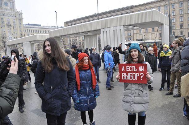 Polina Guzeva oli yksi harvoista kylttiä kantaneista mielenosoittajista.