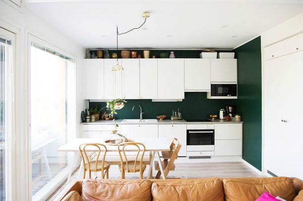 Myös keittiön välitila on kauniin vihreä. Huomaa myös ruokapöydän yläpuolella roikkuva hauska lamppu.