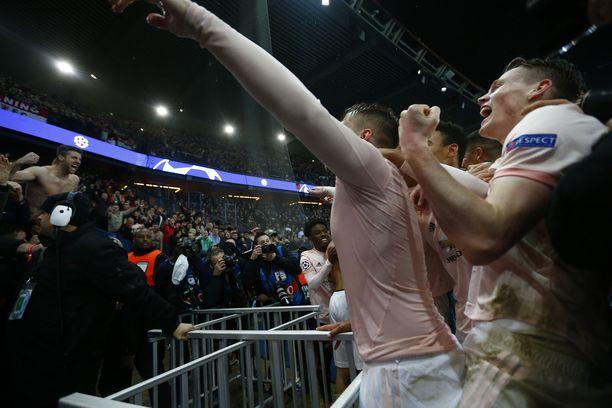 Manchester Unitedin pelaajat juhlimassa kannattajiensa kanssa jatkoonpääsyään keskiviikon trillerin jälkeen.