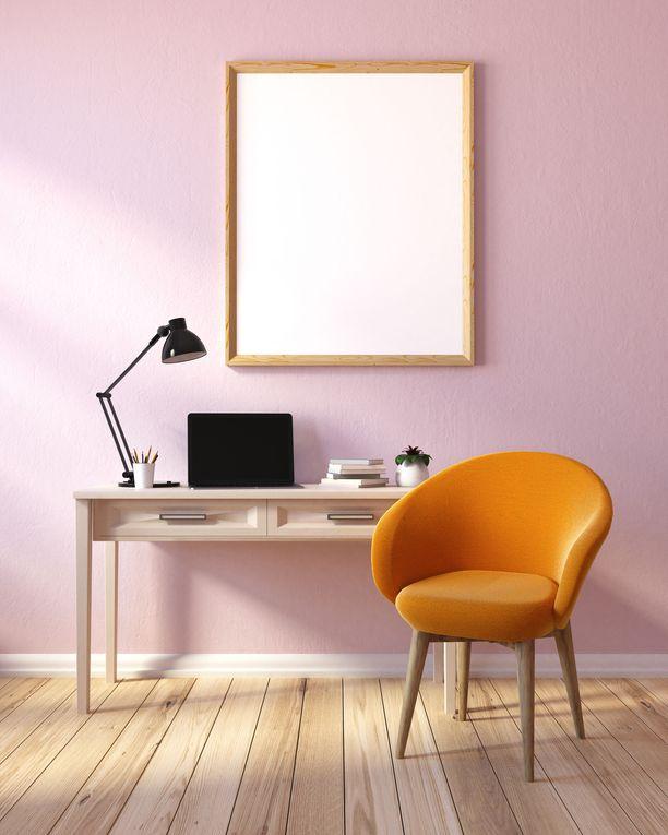 Vaaleanpunainen tehosteseinä on toimiva ratkaisu työhuoneeseen. Oranssi tuoli tuo sopivasti särmää.