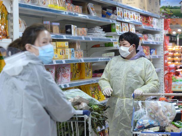"""Wuhanilaisessa marketissa asiakkaat suojautuvat virustartunnalta hengitysmaskien lisäksi """"sadetakein""""."""