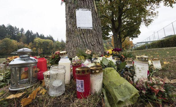 Murhapaikalle on tuotu kukkia ja kynttilöitä.
