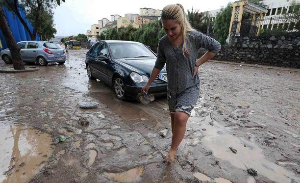 Nainen ylitti mutaista katua Kanariansaarten Gran Canarialla Las Palmasissa.