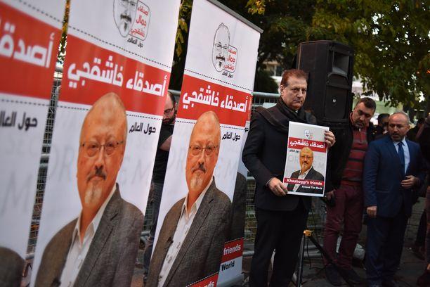 Ihmiset kantoivat Jamal Khashoggin kuvia osallistuessaan mielenosoitukseen Saudi-Arabian Istanbulin-konsulaatin edustalla.