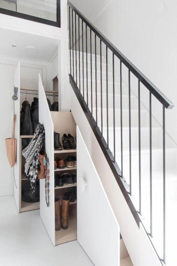 Tässä eteisessä portaiden alapuoli on otettu nerokkaasti käyttöön kätkemällä vaate- ja kenkäkaapit piiloon veto-ovien taakse.