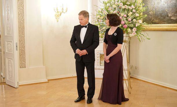 Presidenttipari edusti hymyillen diplomaattipäivällisillä. Presidentin puoliso Jenni Haukio oli pukeutunut hillittyyn, mutta tyylikkääseen liilaan iltapukuun.