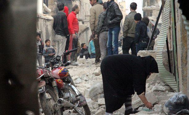 Nainen keräämässä romua maasta toissapäiväisen helikopteri-iskun jäljiltä Syyrian Aleppossa.