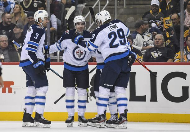 Winnipeg Jetsin Ville Heinola (keskellä) saa Patrik Laineelta (29) ja Tucker Poolmanilta (3) onnittelut ensimmäisestä NHL-maalistaan.