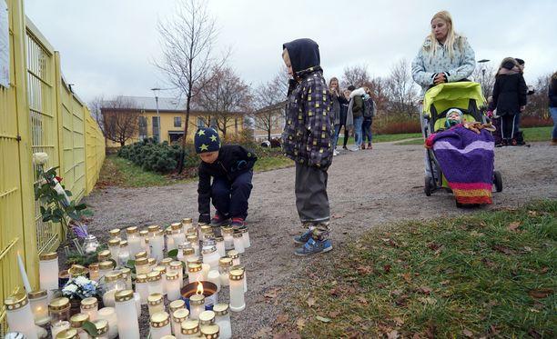 Pamela Pitkänen ja hänen poikansa Rasmus, Elias ja Waltter toivat iltapäivällä puistoon kynttilän.