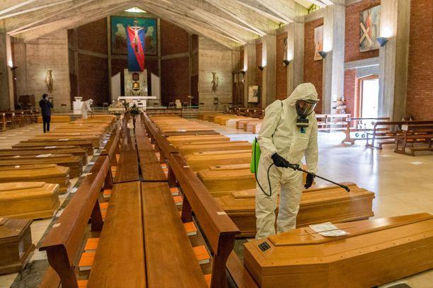 Armeijan lääkintämiehet desinfioivat arkkuja San Giuseppen kirkossa Seriatessa Italiassa.