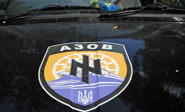 Azov-pataljoonan tunnistaa logosta, joka löytyy univormuista, autoista, t-paidoista, jopa aseista.