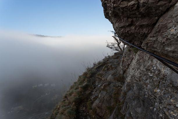 Giddy Edge sumuisella säällä. Polku kulkee kallion seinää kiertävällä kapealla kaistaleella. Turvaa saa rautakaiteesta.