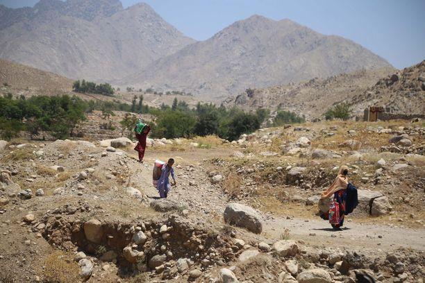 Ihmisiä pakenemassa Taliban-liikkeen ja Afganistanin turvallisuusjoukkojen välistä konfliktia Laghmanin maakunnassa torstaina 8. heinäkuuta.