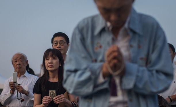 Nainen piti kädessään valokuvaa, kun ihmiset rukoilivat Hiroshiman 70-vuotismuistotilaisuudessa.