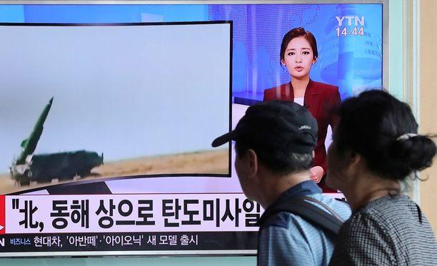 Soulin rautatieasemalla Etelä-Koreassa ihmiset seurasivat uutislähetystä Pohjois-Korean ohjusten laukaisemisesta maanantaina.