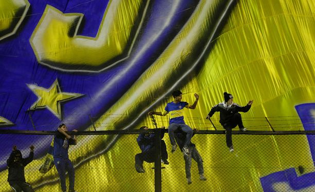 Boca Juniorsin fanit kiipesivät piikkilanka-aidan yli nähdäkseen Carlos Tevezin esittelytilaisuuden valtavan lipun liehuessa taustalla.