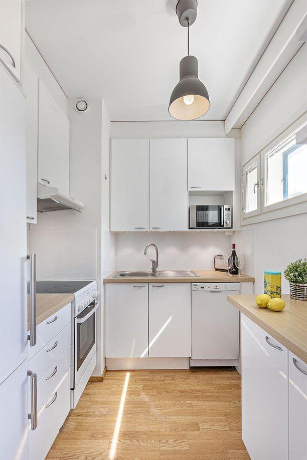 Punavuoressa sijaitsevan asunnon pieni keittiö on valoisa.