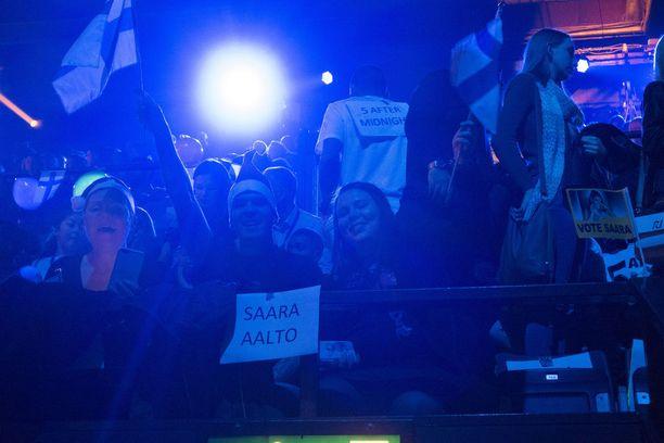 Suomen liput liehuvat yleisössä.