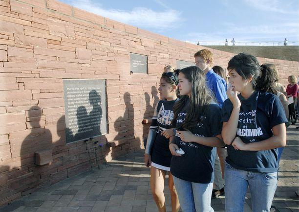 Columbinen oppilaat lukevat kouluampumisessa kuolleiden muistomerkkiin kirjoitettuja tekstejä.